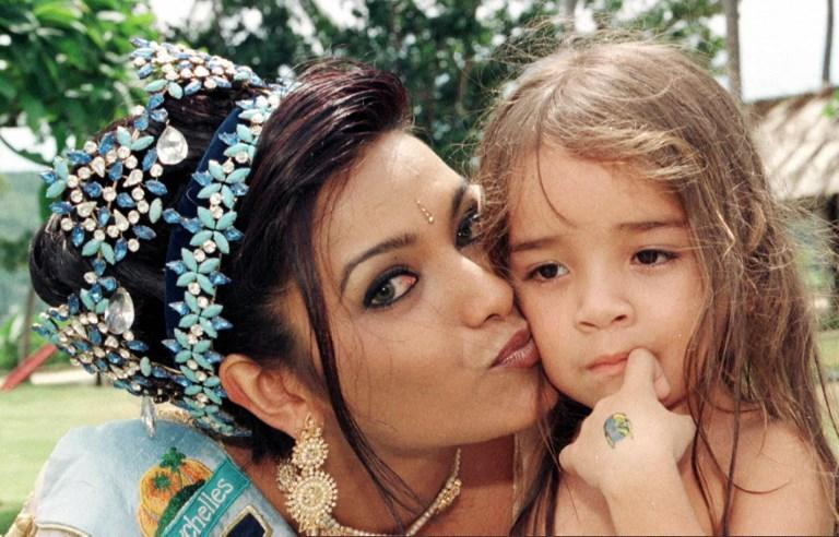 <p>Miss World 1997 Diana Hayden poses with a child a day after she was crowned in Victoria, Seychelles. </p>