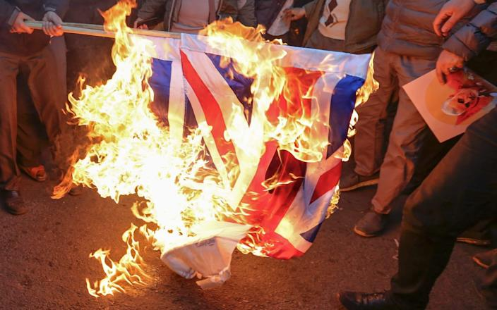 Iranian demonstrators set alight a Union Jack in front of the British embassy in Iran's capital Tehran - AFP