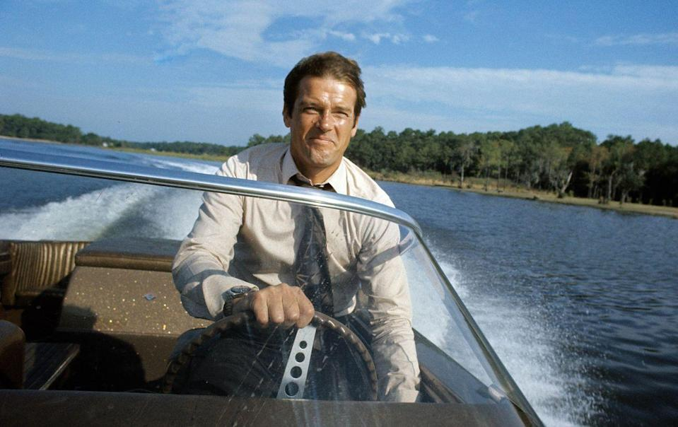 <p>Roger Moore behind the wheel of a speedboat during the filming of <em>Live And Let Die</em> on March 1, 1973 in Kingston, Jamaica.</p>