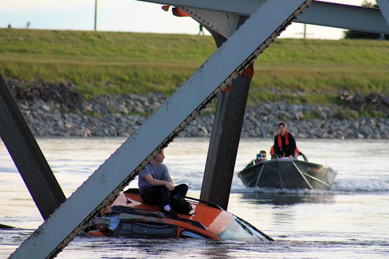 In this photo provided by Francisco Rodriguez, a man is seen sitting atop a car that fell into the Skagit River as a rescue boat approaches after the collapse of the Interstate 5 bridge there minutes earlier Thursday, May 23, 2013, in Mount Vernon, Wash. (AP Photo/Francisco Rodriguez)