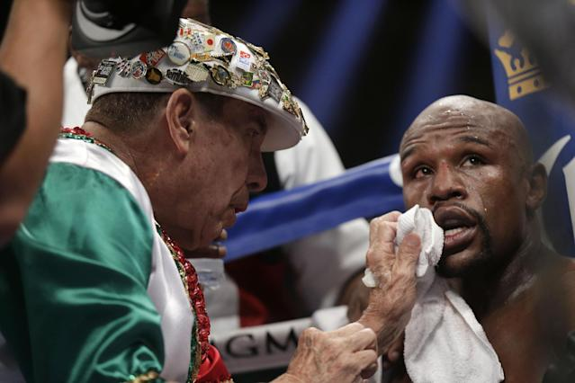 Floyd Mayweather Jr., right, is tended to in his corner during his WBC-WBA welterweight title boxing fight against Marcos Maidana Saturday, May 3, 2014, in Las Vegas. (AP Photo/Isaac Brekken)