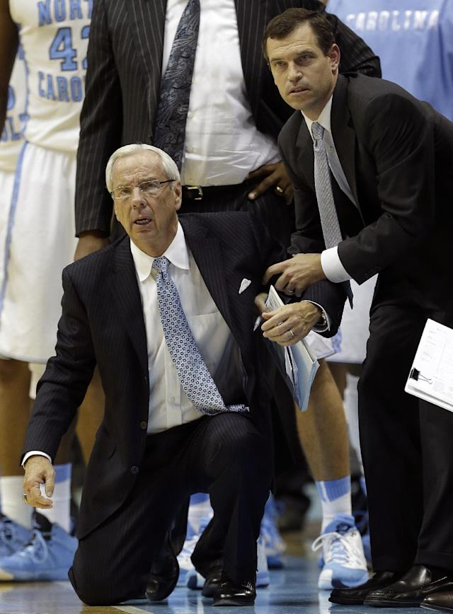 North Carolina coach Roy Williams is helped by assistant coach C.B. McGrath during the second half of an NCAA college basketball game against Belmont in Chapel Hill, N.C., Sunday, Nov. 17, 2013. Belmont won 83-80. (AP Photo/Gerry Broome)