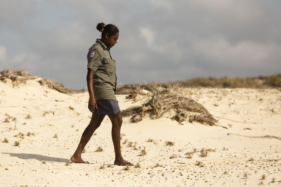 An Indigenous ranger walks along a remote sand dune in Northern Arnhem Land.