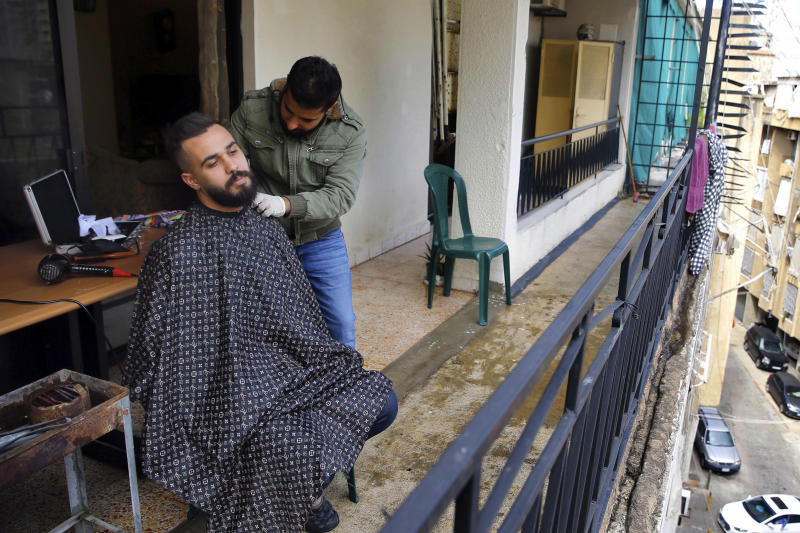 Barber Fouad Lalo cuts hair on the balcony of a customer's home, in Beirut, Lebanon, Thursday, March 26, 2020. Lebanon has been under a government-ordered lockdown since last week in an effort to stem the spread of the coronavirus. (AP Photo/Bilal Hussein)