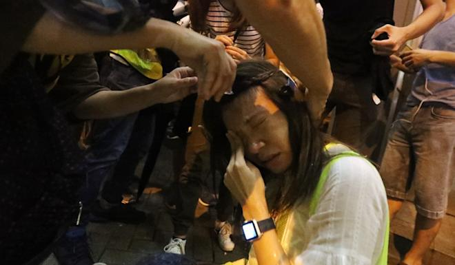 A journalist is helped after being pepper sprayed by police and protesters at Prince Edward on Saturday. Photo: Felix Wong