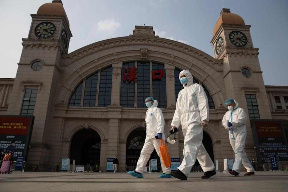 <p>Workers in protective suits walk through central Wuhan</p> (AP)