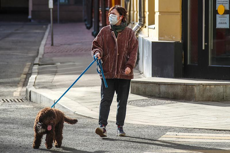 MOSCOW, RUSSIA - APRIL 6, 2020: A woman in a face mask walks her dog during the pandemic of the novel coronavirus (COVID-19). Muscovites are told not to leave home except for essential purposes. As of 6 April 2020, Russia has reported more than 6,300 confirmed cases of the novel coronavirus, with more than 4,400 confirmed cases in Moscow. Since 30 March 2020, Moscow has been on lockdown in connection with the pandemic. The Russian government announced a paid period off work for employed people and school holidays, which is expected to last till the end of April. Valery Sharifulin/TASS (Photo by Valery Sharifulin\TASS via Getty Images)