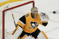 Pittsburgh Penguins goaltender Tristan Jarry reaches for the puck the first period of the team's NHL hockey game against the Philadelphia Flyers, Thursday, March 4, 2021, in Pittsburgh. (AP Photo/Keith Srakocic)