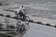 A man rides his bicycle along Marine Drive as rain falls in Mumbai on June 3, 2020. (Photo by PUNIT PARANJPE/AFP via Getty Images)