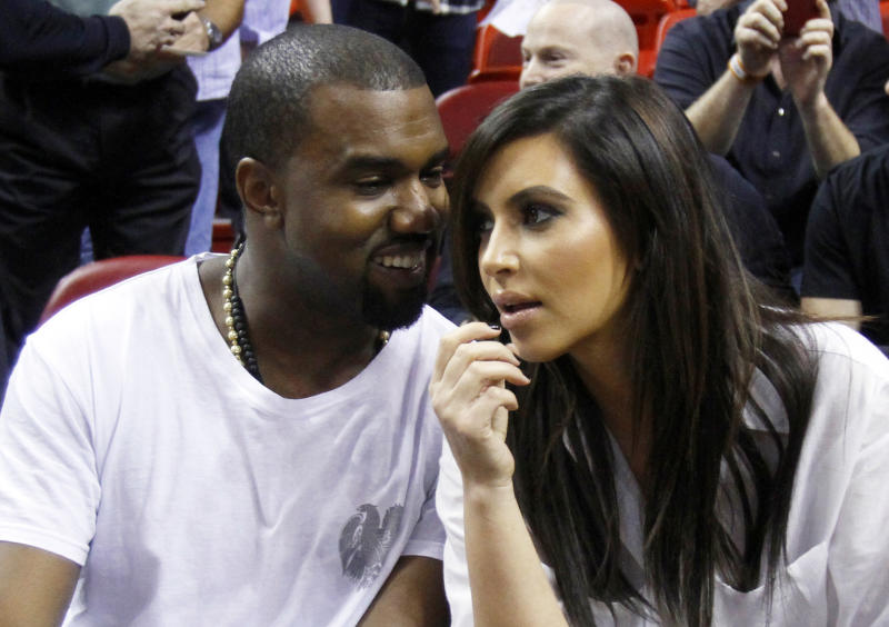 FILE - This Dec. 6, 2012 file photo shows singer Kanye West, left, talks to his girlfriend Kim Kardashian before an NBA basketball game between the Miami Heat and the New York Knicks in Miami. A birth certificate released by the Los Angeles County Dept. of Public Health shows that the couple's daughter North west, was born on Saturday, June 15, 2013 at Cedars-Sinai Medical Center in Los Angeles. (AP Photo/Alan Diaz, file)