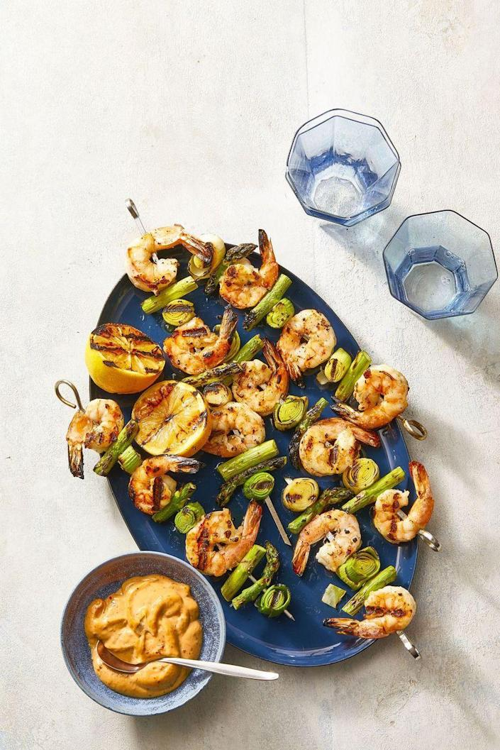 """<p>This bright and colorful dish is easy to grill and sure to be a crowdpleaser, especially if you're hosting some health-conscious guests. </p><p><em><strong><a href=""""https://www.womansday.com/food-recipes/a36040238/charred-shrimp-leek-and-asparagus-skewers-recipe/"""" rel=""""nofollow noopener"""" target=""""_blank"""" data-ylk=""""slk:Get the Charred Shrimp & Asparagus Skewers recipe"""" class=""""link rapid-noclick-resp"""">Get the Charred Shrimp & Asparagus Skewers recipe</a>.</strong></em></p>"""