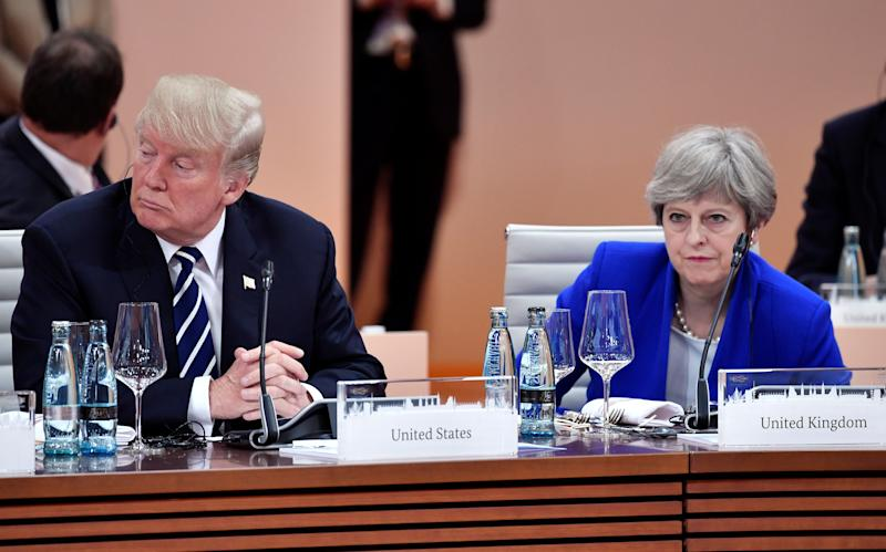 Trump and British Prime Minister Theresa May wait at the start of the first working session of the G-20 meeting in Hamburg, Germany, on July 7. (John MacDougall/Pool/Reuters)