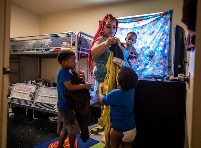 Lexus Ikeard, center, holding her son Troi Ensley, helps her other sons Travis and Noah Lawless get set up with clothes for after their baths at their residence in Nashville on Wednesday, August 25, 2021.