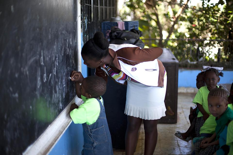 In this Nov. 13, 2013, photo, a teacher works with children at the U.S.-based Church of Bible Understanding orphanage in Kenscoff, Haiti. The orphanage is run by a Christian missionary group funded by the Olde Good Things antique store on Manhattan's Upper West Side. While many other orphanages also have failed the Caribbean country's new national standards, and conditions are far worse in some, the group's three-story building on the hilly outskirts of Port-au-Prince stands out because it's run by an organization with such an unusual, and successful fundraising operation. The failure to meet the standards would seem to contradict their financial position.(AP Photo/Dieu Nalio Chery)