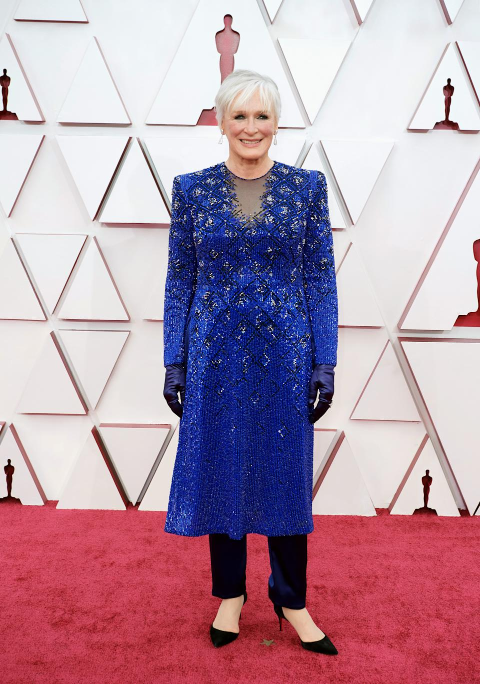 Glenn Close slips into a dazzling blue tunic dress with black trousers and matching court heels at the 93rd Oscars in Los Angeles on Sunday, April 25, 2021. (Getty Images)