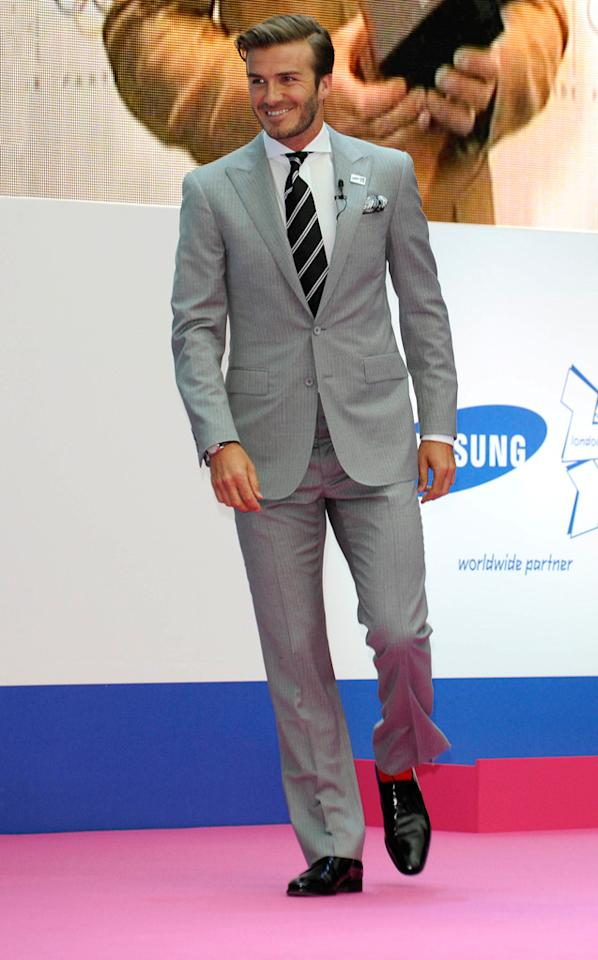 "David Beckham donned a dapper suit, striped tie, and a scruffy mug as he helped kick off Samsung's Olympic campaign in London's Canary Wharf district. Are you liking his slick coif and gray getup as much as I am? Steve Finn/<a href=""http://www.splashnewsonline.com"" target=""new"">Splash News</a> - June 13, 2011"
