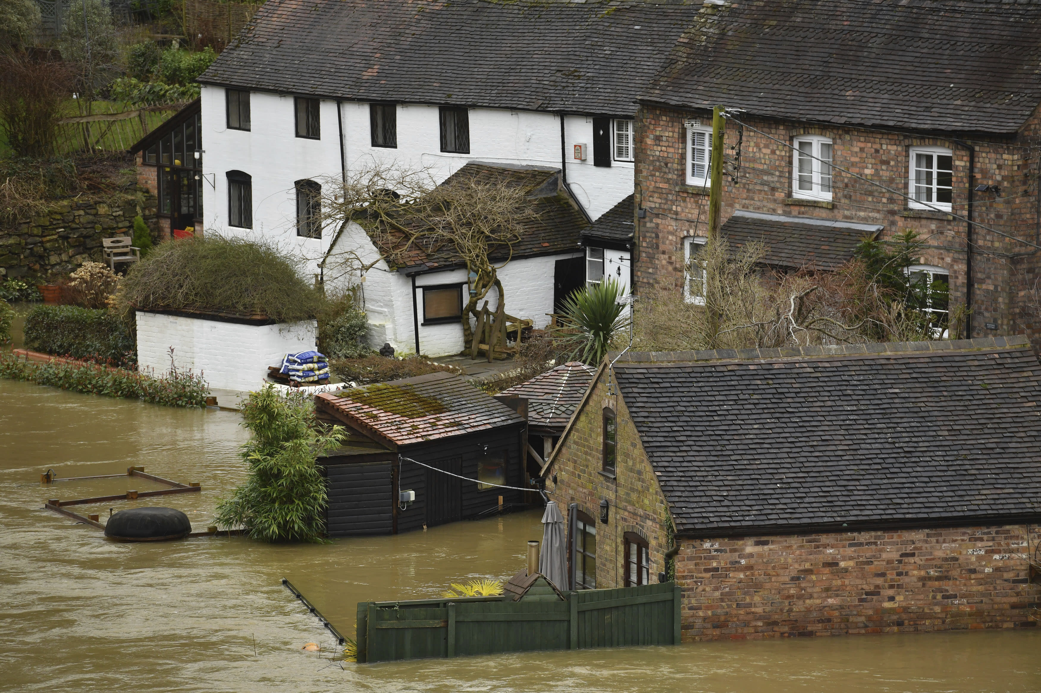 Houses surrounded are inundated by flood water after heavy rains breached normal watercourses in the area of Ironbridge, England, Wednesday Feb.19, 2020. Flood-hit communities are braced for further heavy rain as river levels continue to threaten to breach barriers, in the aftermath of Storm Dennis which has swept northern Europe. (Jacob King/PA via AP)