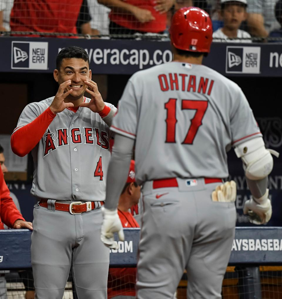 Los Angeles Angels' Jose Iglesias (4) greets Shohei Ohtani at the dugout after Ohtani's solo home run off Tampa Bay Rays' Andrew Kittredge during the first inning of a baseball game Friday, June 25, 2021, in St. Petersburg, Fla. (AP Photo/Steve Nesius)