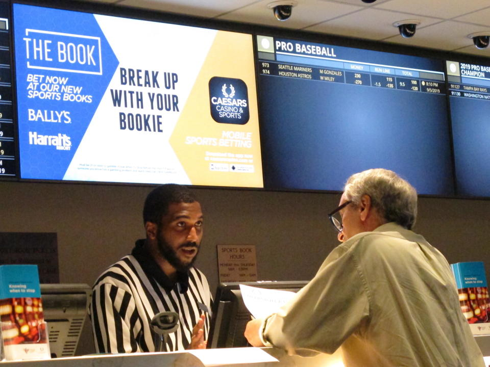 FILE - This Sept. 5, 2019, file photo shows a gambler making a sports bet at Bally's casino in Atlantic City, N.J. The online sports betting company FanDuel will open an in-person sports book at Bally's casino in Atlantic City once the casino's sale to a Rhode Island company is finalized. FanDuel told The Associated Press on Wednesday, Oct. 28, 2020, that it has plans for a temporary sports betting facility in the casino before the end of the year, and will build a permanent sports book on the center of the casino floor next spring. (AP Photo/Wayne Parry, File)