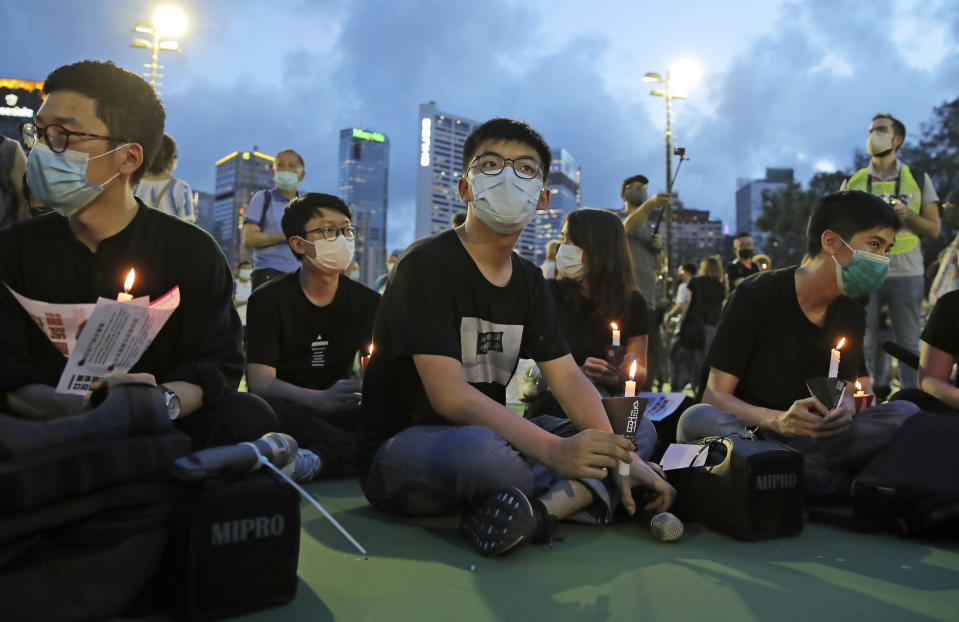In this June 4, 2020, photo, democracy activist Joshua Wong, center, and Nathan Law, left, hold candles during a vigil to remember the victims of the 1989 Tiananmen Square Massacre at Victoria Park in Hong Kong. Wong will face an additional 10 months in jail for participating in an unauthorized Tiananmen vigil held last year to commemorate the 1989 crackdown on protesters in Beijing, as Hong Kong authorities continue tightening control over dissent in the city. (AP Photo/Kin Cheung)