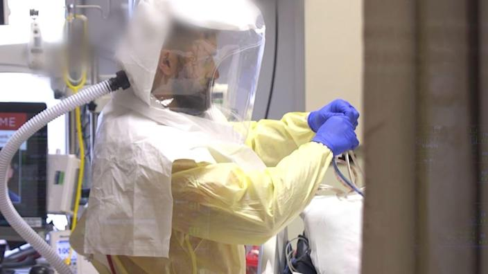 """<div class=""""inline-image__caption""""><p>""""Stepheno Zollos, RN, wears a PAPR (Powered Air Purifying Respirator) while caring for a patient in the Intensive Care Unit at Saint Alphonsus Regional Medical Center in Boise, ID.""""</p></div> <div class=""""inline-image__credit"""">Courtesy Saint Alphonsus Health System</div>"""