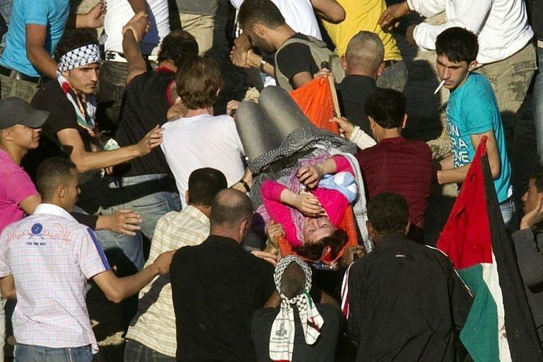 Demonstrators carry a wounded fellow protestor who was hit by Israeli fire while trying to cut through a line of barbed wire and head into the Israeli-annexed Golan Heights. Israeli troops opened fire on Sunday as protesters from Syria stormed a ceasefire line in the occupied Golan Heights, with Damascus saying 23 demonstrators were killed