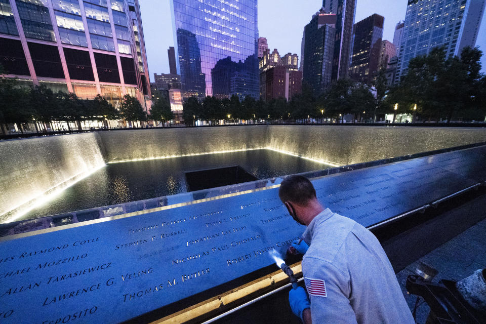 """Kevin Hansen, an engineer at the September 11 Memorial, uses a torch to clean and burnish the names cut into the metal plates that border the south pool, Wednesday, Aug. 4, 2021 in New York. """"I believe this place brings people to see that there is evil in the world but it can be overcome,"""" Hansen says. """"You're looking down and you are trying to realize that this place is a sacred place and has to be remembered."""" (AP Photo/Mark Lennihan)"""