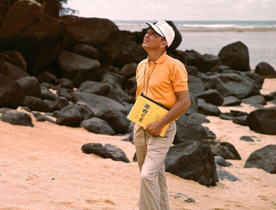 <p>Frank Sinatra takes a break from studying the script for <em>None But the Brave</em>. </p>
