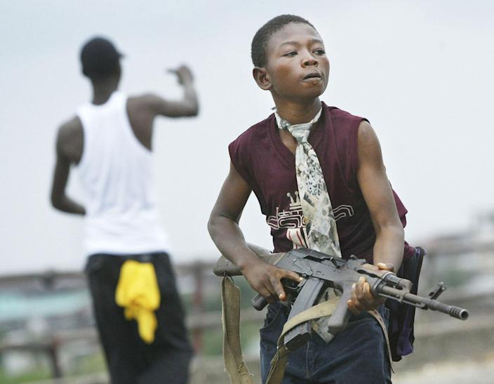 <p>A child Liberian militia soldier loyal to the government walks away from firing on rebel forces across a key bridge while another taunts them July 30, 2003 in Monrovia, Liberia. Sporadic clashes continue between government forces and rebel fighters in the fight for control of Monrovia. (Photo by Chris Hondros/Getty Images) </p>