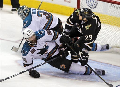 Dallas Stars center Steve Ott (29) tumbles over San Jose Sharks defenseman Brent Burns (88) and goalie Antti Niemi (31), of Finland, during the second period of a NHL hockey game on Tuesday, April 3, 2012, in Dallas. †(AP Photo/John F. Rhodes)