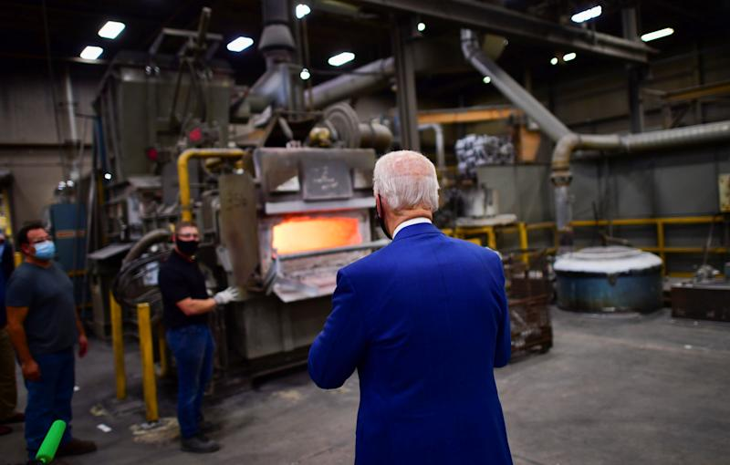 Democratic U.S. presidential nominee and former Vice President Joe Biden walks towards two workers waiting at an aluminum forge as he tours Wisconsin Aluminum Foundry before delivering remarks at a campaign event in the factory in Manitowoc, Wisconsin, U.S., September 21, 2020. REUTERS/Mark Makela