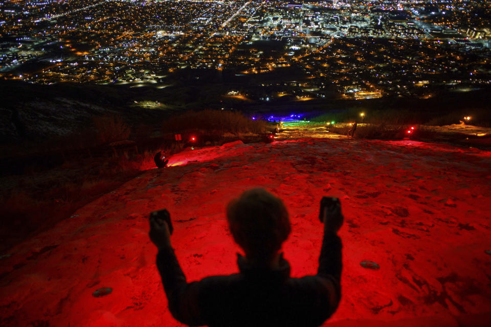 """FILE - In this Thursday, March 4, 2021. file photo, a group of people, including many BYU students shine Pride colors on the Y on the mountain above BYU in Provo, Utah. Students at Brigham Young University illuminated the letter """"Y"""" on a mountain overlooking the Provo campus on Thursday with rainbow colors in a display meant to send a message to the religious school. (Trent Nelson/The Salt Lake Tribune via AP, File)"""