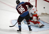 Colorado Avalanche right wing Mikko Rantanen, left, scores a goal past Calgary Flames goaltender Mike Smith to tie the score in the third period of Game 4 of an NHL hockey playoff series Wednesday, April 17, 2019, in Denver. The Avalanche won 3-2 in overtime. (AP Photo/David Zalubowski)