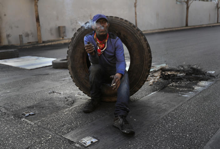 A protester smokes a cigarette and sits on a tire as he aims to block a road during a protest, in Beirut, Lebanon, Monday, March 8, 2021. The dayslong protests intensified Monday amid a crash in the local currency, increase of consumer goods prices and political bickering between rival groups that has delayed the formation of a new government. (AP Photo/Hussein Malla)