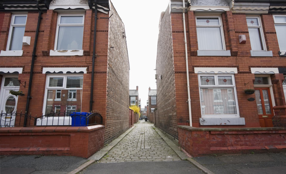 """Street of row houses / terraced houses with alleyway between blocks. This is Moss Side, Manchester, UK."""