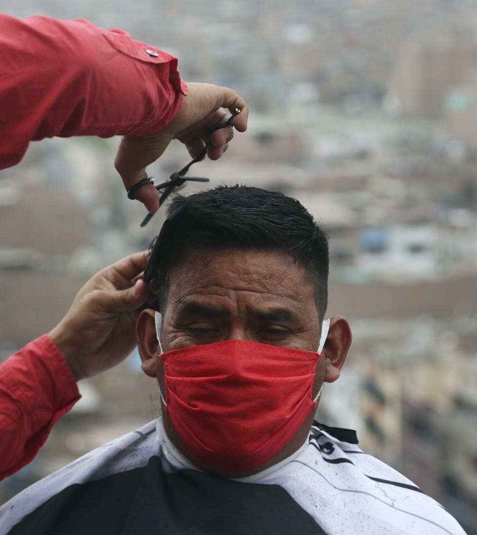 Josue Yacahuanca clips the hair of a resident free of charge, at the top of a hill in the San Juan de Lurigancho neighborhood of Lima, Peru, Friday, June 19, 2020. Peru has roughly 150,000 barbers, but Yacahuanca is among a few who've decided to offer his services to those most in need. (AP Photo/Martin Mejia)