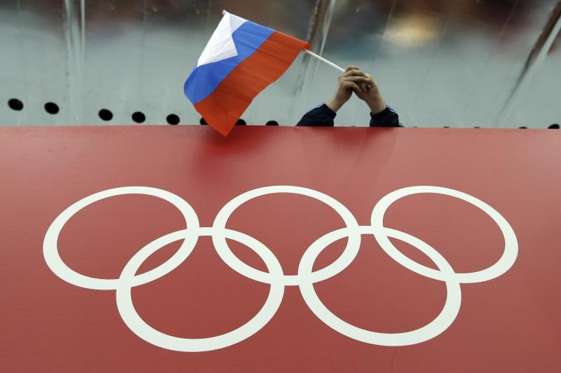 FILE - In this Feb. 18, 2014, file photo, a Russian flag is held above the Olympic Rings at Adler Arena Skating Center during the Winter Olympics in Sochi, Russia.  A World Anti-Doping Agency (WADA) panel on Monday Nov. 25, 2019, has recommended Russian athletes be forced to compete as neutrals at the 2020 Olympics in Tokyo and other major upcoming events. (AP Photo/David J. Phillip, File)