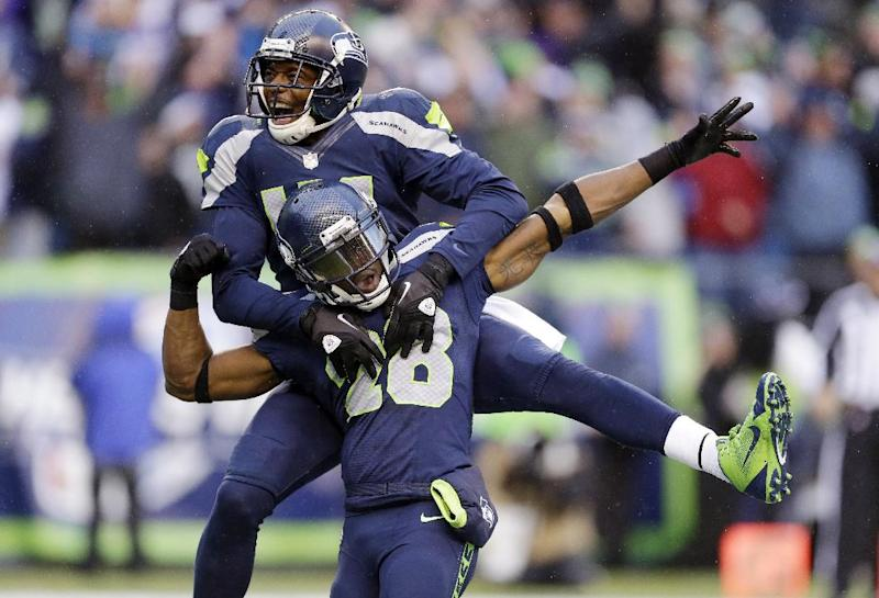 Seattle Seahawks' Byron Maxwell, top, leaps on the back of Walter Thurmond after Thurmond intercepted and scored against the Minnesota Vikings in the second half of an NFL football game Sunday, Nov. 17, 2013, in Seattle. (AP Photo/Ted S. Warren)