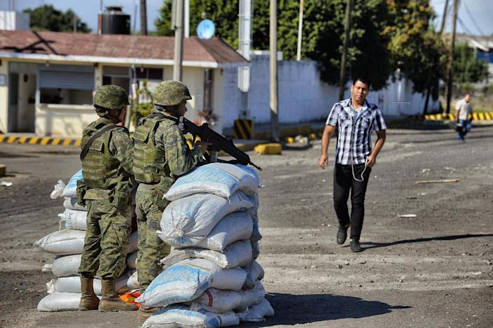 Mexican soldiers stand at a checkpoint at the entrance of the Apatzingan community in the state of Michoacan, Mexico on January 12, 2015 (AFP Photo/Alfredo Estrella)