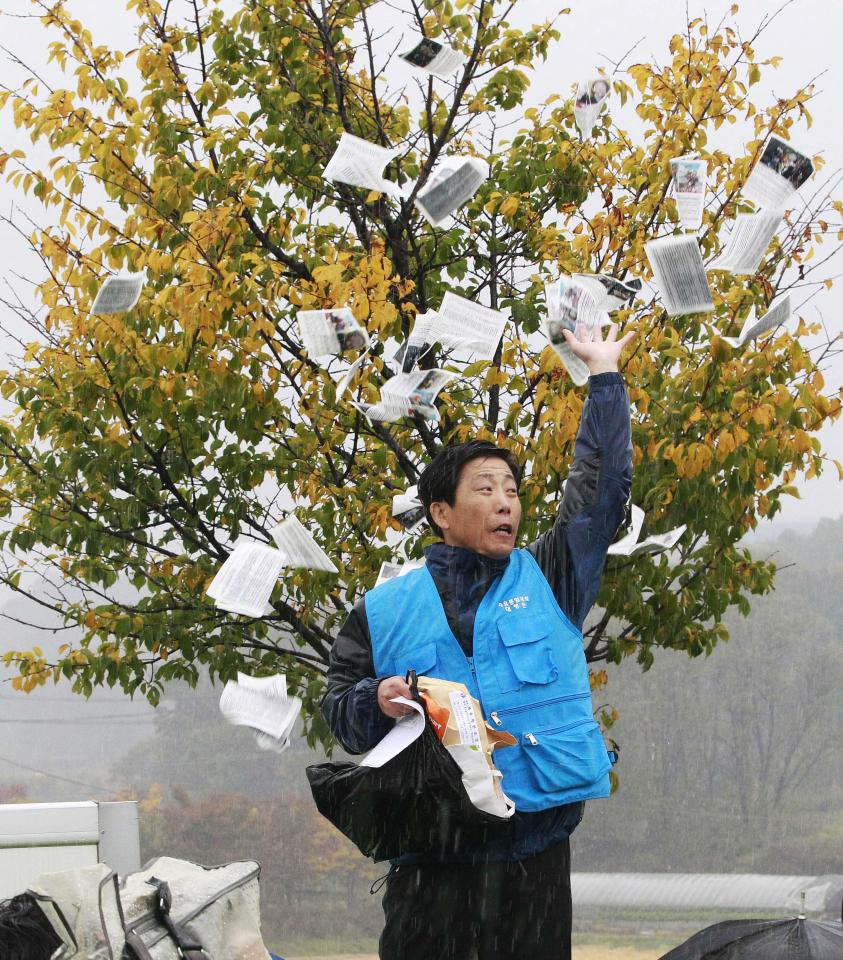 North Korean defector Park Sang-hak hurls anti-North Korea leaflets as police block his planned rally on a road in Paju near demilitarized zone, South Korea, Oct. 22, 2012. South Korea has banned activists from launching propaganda leaflets to North Korea after North Korea threatened to attack.(AP Photo/Ahn Young-joon)