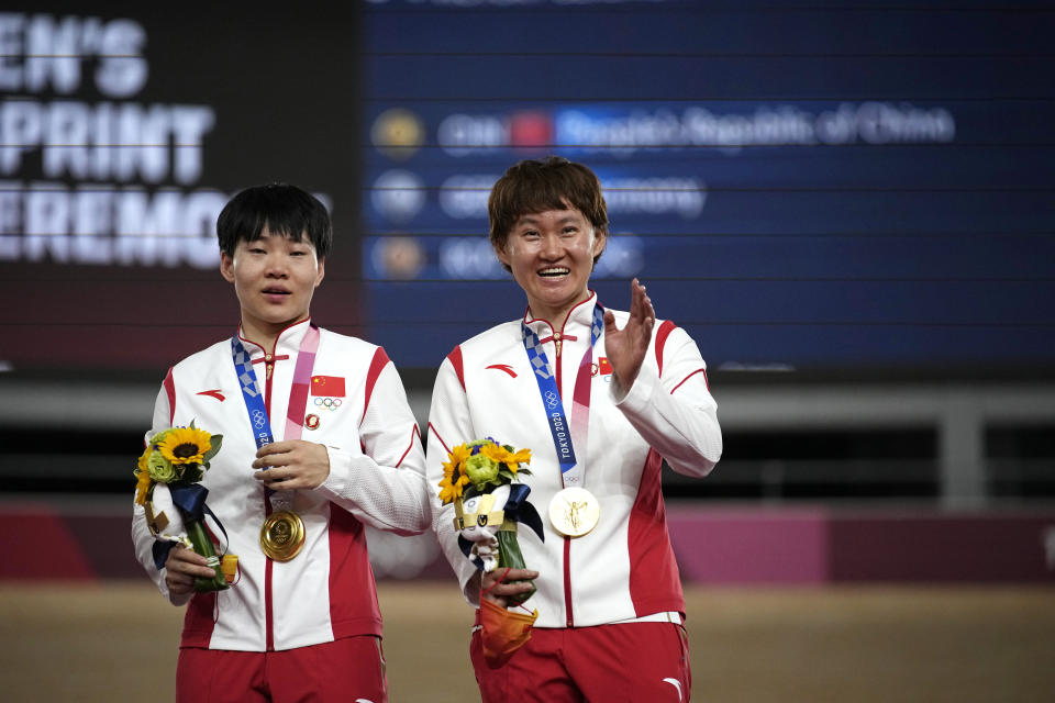 Shanju Bao, left, and Tianshi Zhong of Team China hug celebrate their gold medals during a medal ceremony for the track cycling women's team sprint finals at the 2020 Summer Olympics, Monday, Aug. 2, 2021, in Izu, Japan. (AP Photo/Christophe Ena)