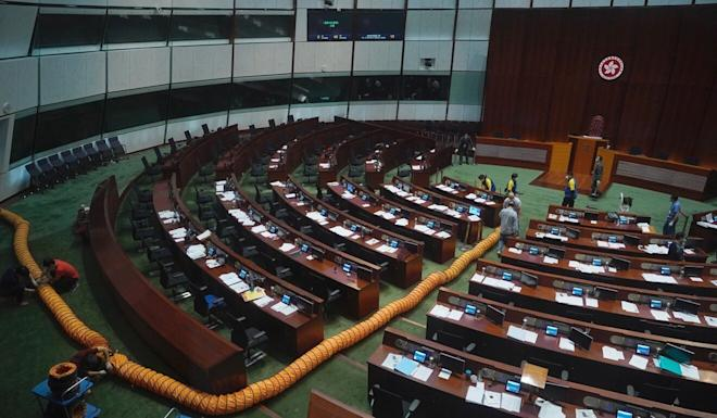 Staff install a ventilation pipe at the main chamber of the Legislative Council after an opposition member dropped a pot of pungent liquid there in June. Photo: AP