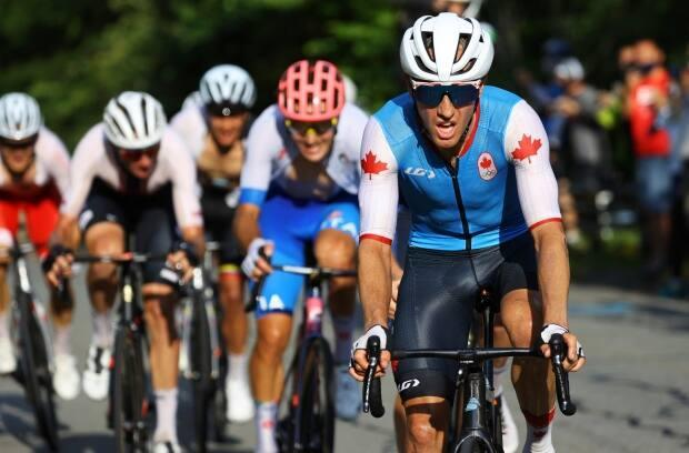 Canada's Michael Woods leads the pack in the climbing section of the men's cycling road race at the Tokyo Olympics on Saturday. (Tim de Waele - Pool/The Associated Press - image credit)