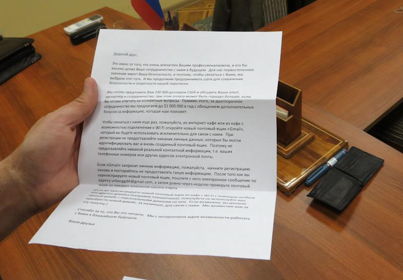 CLARIFIES THAT THIS IS CLAIMED  BY THE FSB TO BE A RECRUITING LETTER  In this handout photo  provided by the FSB, acronym for Russian Federal Security Service, which they claim is a recruiting letter carried by a man claimed by FSB to be Ryan Fogle, a third secretary at the U.S. Embassy in Moscow, when he was detained, is shown in the FSB offices in Moscow, early Tuesday, May 14, 2013. Russia's security services say they have caught a U.S. diplomat who they claim is a CIA agent in a red-handed attempt to recruit a Russian agent. Ryan Fogle, a third secretary at the U.S. Embassy in Moscow, was carrying special technical equipment, disguises, written instructions and a large sum of money when he was detained overnight, the FSB said in a statement Tuesday. Fogle was handed over to U.S. embassy officials, the FSB, said. (AP Photo/FSB Public Relations Center)