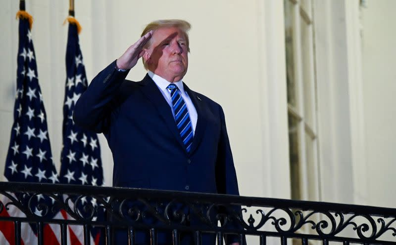 FILE PHOTO: U.S. President Donald Trump poses without face mask as he returns to the White House after being hospitalized at Walter Reed Medical Center for coronavirus disease (COVID-19), in Washington