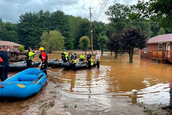 In this image provided by New Hanover County Fire Rescue, members of North Carolina's Task Force 11, based in New Hanover County, are shown during rescue efforts in Canton, N.C, on Tuesday, Aug. 17, 2021.