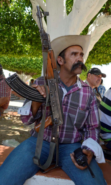A member of a self-defense group sits with his weapon as he waits during the first day of weapons registration in Coalcoman, Mexico, Monday, 28, 2014. The confusing proliferation of false self-defense groups in Michoacan and instances of alleged looting and killings by legitimate vigilantes have led the federal government to tell the vigilantes they have to demobilize by May 10 but the vigilantes, who usually carry assault rifles that are prohibited for civilian use, only have to turn in their heaviest weapons, such as .50-caliber sniper rifles. They will be allowed to keep, but not publicly carry, AR-15 and AK-47 assault rifles, as long as they register them with the army. (AP Photo/Agencia Esquema)