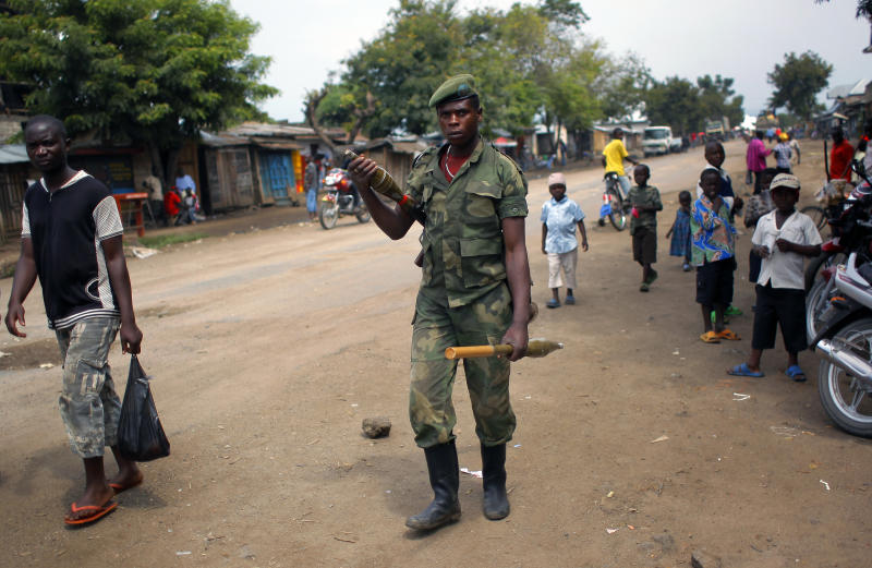 FILE - In this Aug. 5, 2012 file photo, an M23 rebel walks the streets of the North Kivu town of Rubare, near Rutshuru, 75 km (48 miles) north of Goma, Congo. Nearly 30 people have been kidnapped in eastern Congo by the M23 rebels in their fief of Rutshuru since the beginning of April, said a community leader on Wednesday, May 8, 2013. The kidnappings appear to be for ransom, a new and worrying trend in Congo's lawless east. (AP Photo/Jerome Delay, File)