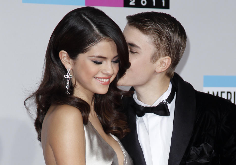 Singer Justin Bieber kisses his girlfriend, singer Selena Gomez, as they arrive at the 2011 American Music Awards in Los Angeles November 20, 2011. REUTERS/Danny Moloshok  (UNITED STATES - Tags: ENTERTAINMENT PROFILE) (AMA-ARRIVALS)