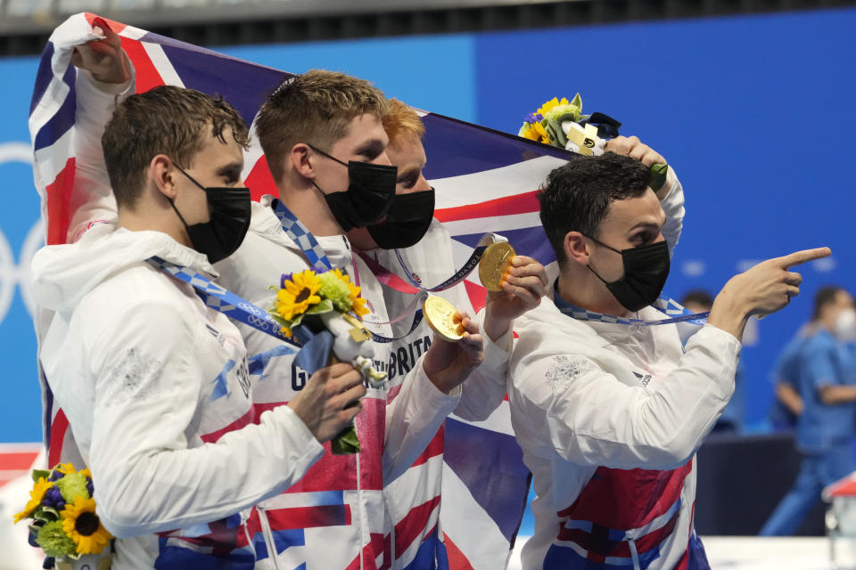Britain's men's 4x200-meters freestyle relay team of Tom Dean, James Guy, Matthew Richards, and Duncan Scott celebrate after winning the gold medal at the 2020 Summer Olympics, Wednesday, July 28, 2021, in Tokyo, Japan. (AP Photo/Martin Meissner)